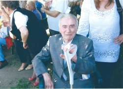 Eugenio Cassanmagnago (1924-2014), a mezza figura, seduto, al parco di Villa La Gioiosa. Alle spalle cittadini convenuti alla cerimonia.