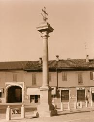 Piazza San Vittore: in primo piano la Colonna della Peste, un piccolo pezzo di piazza, edifici ed un portone sulla sinistra