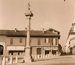 Piazza San Vittore: in primo piano la Colonna della Peste, un piccolo pezzo di piazza, edifici e Via Madonna