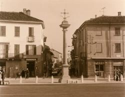 Piazza San Vittore: in primo piano la Colonna della Peste, un piccolo pezzo di piazza, edifici e Via Matteotti